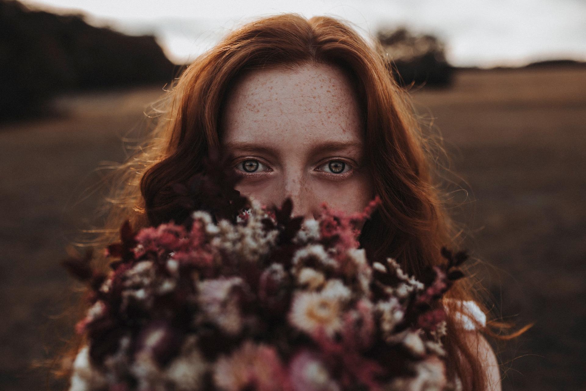 Rothaarige junge Frau mit Blumenstrauß. Fokus auf Augen